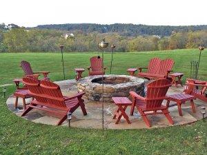 Outdoor furniture around stone firepit in field