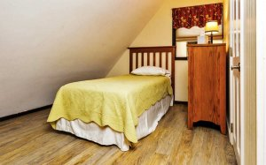 A small bed in an upstairs room