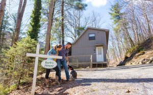 The innkeepers and their dog near a cabin with sign that says Barb's House