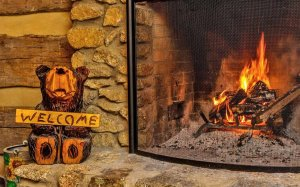 Carved bear with a welcome sign adjacent to a fireplace