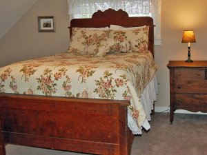 Bed with floral covers and reddish wooden frame