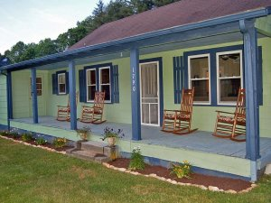 A green cottage with blue trim