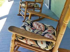 Two wooden rocking chairs with floral pads