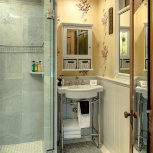 Shower in bathroom with sink and mirror
