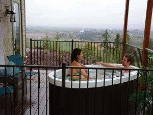 A couple sitting in a hottub on the balcony