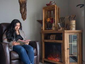 Woman sitting in chair reading a book next to the fireplace