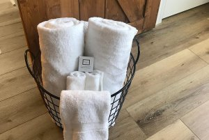 Rolled Towels in a Basket with Soaps