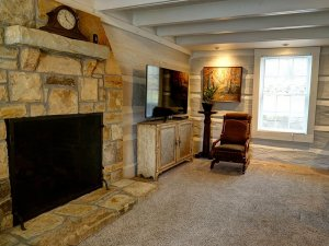Stone fireplace next to television in living room