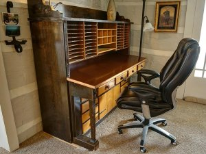 Desk with plenty of slots and drawers in corner of room