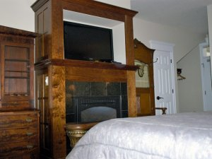 Television above fireplace at end of bed