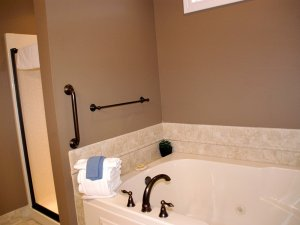Bathtub next to glass shower door