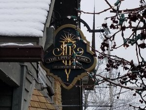 Upper Rooms sign hanging from snowy roof