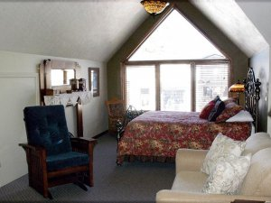 Cushioned rocking chair next to twin-sized bed by window