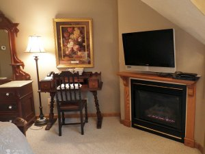 Chair and desk next to fireplace and television