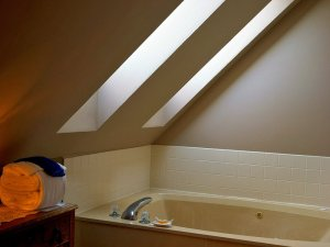 Whirlpool tub below vaulted ceiling and windows