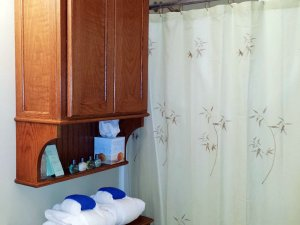 Shower curtains in bathroom next to cabinet