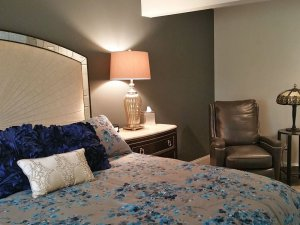 Bed, lamp, and reclining leather seat in bedroom