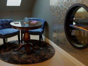 Club chairs at small round table next to circular fireplace
