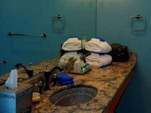 Stack of towels on sink countertop by mirror