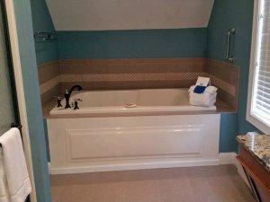 Bathtub next to window in bathroom