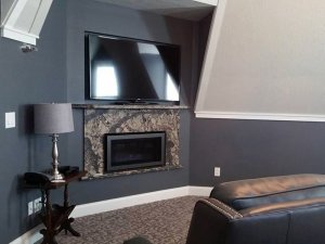 Wall-mounted television above stone fireplace across from leather couch