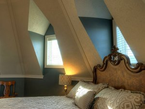 Bed against wall and large windows