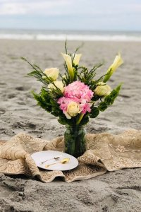 Bouquet of flowers on a towel in the sand