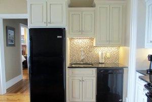 Fridge and sink under cupboards in kitchen