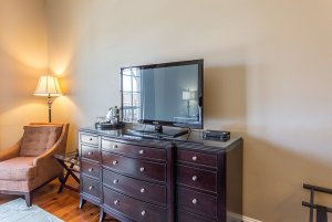 Television on dresser next to cushioned seat