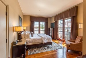 King-sized bed across from large window with drapes