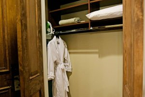 Bathrobe and pillow in closet with shelves