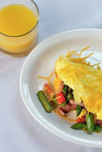 Omelete on plate next to orange juice