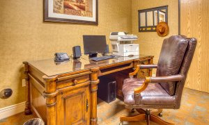 Leather office chair at wood desk with computer