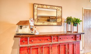 Mirror and small wood house above cabinet