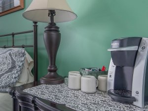 Bedside table with coffee maker, lamp, and candles