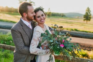 Smiling bride and groom hear fence