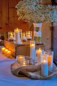 candles on burlap near vase of flowers
