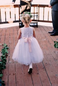 flower girl in pink dress walking down the aisle