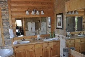 Double sinks next to large wall mirror and whirlpool tub