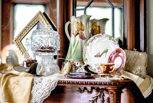 Glass and porceline dishes on mantle with mirror