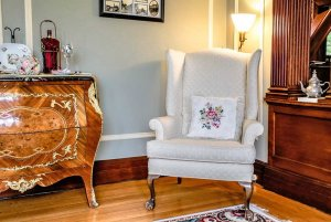 Floral pillow on seat next to cabinet and chinaware