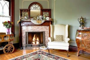 Fireplace and mantle next to cushioned seat sitting room