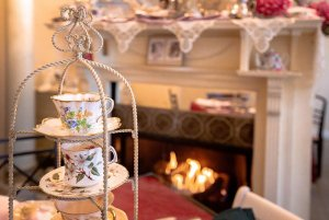 Fireplace and mantle behind teacups in display tower
