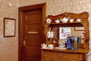 Coffee maker and tea cups on cabinet with mirror