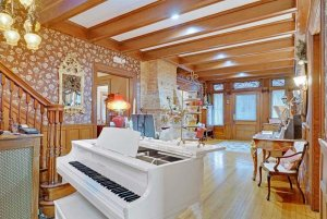 Grand piano in foyer with stone fireplace and seats
