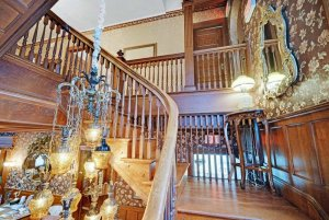 Chandelier hanging next to rails on staircase