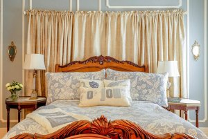 Queen bed next to lamps and drawn curtains