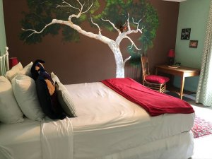 Queen bed in separate room with decorated wall