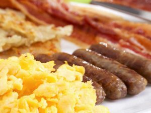 Scrambled eggs, bacon, hashbrowns, and sausage on plate