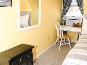 Gas fireplace next to mirror, desk, chair, and bed
